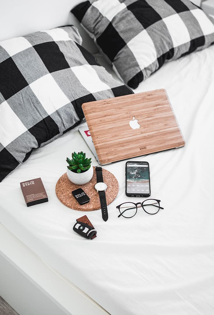 macbook, coffee, smartphone and other items on bed